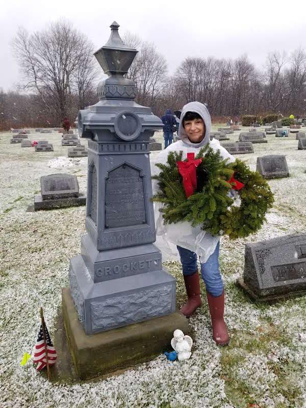 MFG Tray teammate putting a wreath on head stone for Wreaths Across America